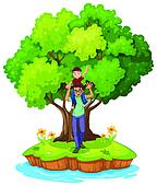A young boy carried by his father near the big tree