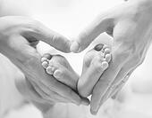 Tiny Newborn Baby's Feet on Female Heart Shaped Hands Closeup