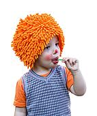Clown child eating a lollipop on white background