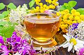 Tea from flowers in glass cup on board