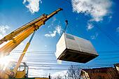 Industrial Crane operating and lifting an electric generator