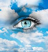 Beautiful blue eye against blue clouds - Spiritual concept