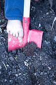 Bare foot of a little child digging with a spade