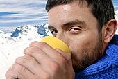 young attractive man outdoors drinking cup of coffee or tea in cold winter