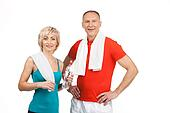 pretty man and woman standing in gym. aged lady holding water and smiling