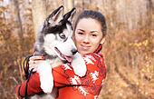 Beautiful young woman hugging huskies puppy for a walk in the park
