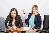 Joyful girl in the office with a phone in his hand close to the unhappy colleague