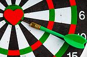 Black white target with dart in heart love symbol as bullseye