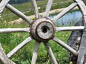 Old wooden wagon wheel with alpine lake and pasture in background