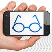 Studying concept: Hand Holding Smartphone with Glasses on display