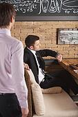 young man sitting in cafe waiting for somebody. handsome guy looking at his handwatches while waiter standing near