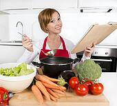 attractive cook woman preparing vegetable stew soup reading recipe cookbook at domestic kitchen