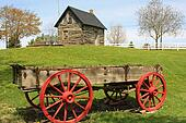 Pioneer log cabin and wooden wagon