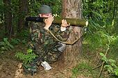 Young man in a camouflage shoots from a grenade launcher