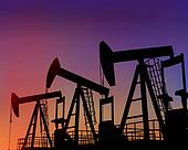 Three oil wells in the desert at dusk