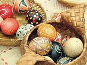 Multicolored easter eggs in straw pot.