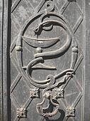 Snake with a cup, symbol of medicine, at the metal gate