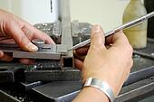 metalworker measuring a metal piece for drilling