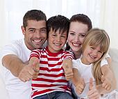 Portrait of smiling family sitting on sofa together with thumbs up