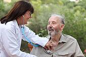 dr with stethoscope checking senior patient.