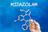 Hand with pen drawing the chemical formula of Midazolam