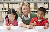 Kindergarten teacher helping students with writing skills