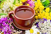 Tea from flowers in clay cup on board
