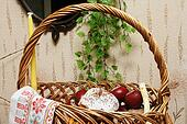 Basket with Easter cake, Easter eggs and a candle