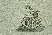 Stone carving of a man in a wheelchair