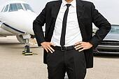 Entrepreneur Standing In Front Of Private Jet And Car