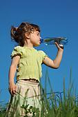 girl standing in grass drinks water from  plastic bottle