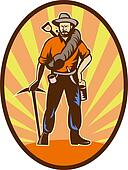 Miner, prospector or gold digger with pick axe and shovel standing front
