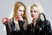 women in latex with handcuffs and whip
