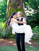 Caucasian groom carrying his biracial bride outdoors, with a kis