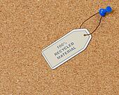 recycled material tag attached to corkboard with thumb tack