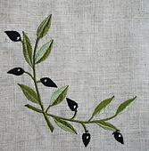 Embroidery of olive branch on linen beige fabric