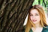 Beautiful girl standing along big tree