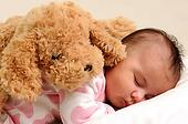 baby with white and pink sleepwear, sleeps with brown toy dog on her back