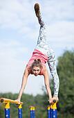 Agile young gymnast balancing on cross bars
