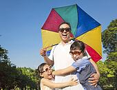 Father holding a colorful umbrella and hug two daughter