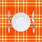 Dinner plate, knife and fork over orange tablecloth