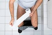 Man In Toilet Holding Tissue Paper
