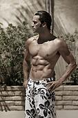 Stylized portrait of a beautiful muscular wet male model outdoors in swim trunks