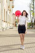 Beautiful fashion girl with red balloon on the street