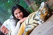 Teen girl playing with tiger cub inside cage
