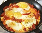 Fried eggs with tomato on the pan