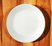 White dinner plate on wood table