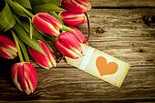 Bouquet of red tulips with a red heart gift tag