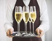 Professional male waiter in uniform serving champagne. DOF.
