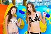 Two smilng women in bikini standing near water slide in the aqua park and holding rubber ring